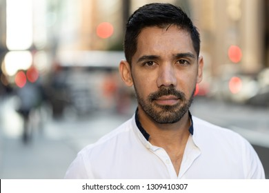 Young Latino Hispanic man in city serious face portrait