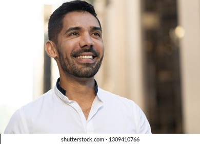 Young Latino Hispanic man in city smile happy face portrait