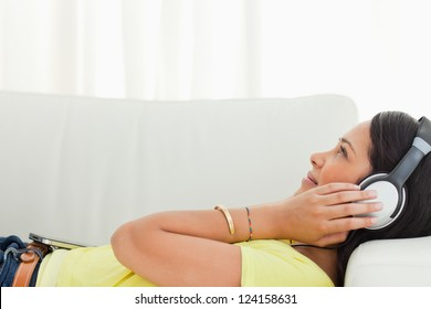 Young Latino listening music with a smartphone while lying on a sofa