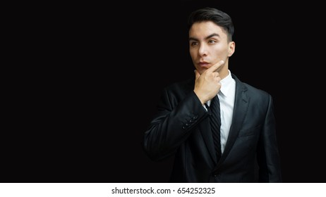 Young latino man in black suit, white shirt, black tie in thoughtful pose with his hand on jaw