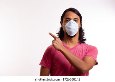 young latino man with mask on white background points his hand to the right. Quarantine concept.