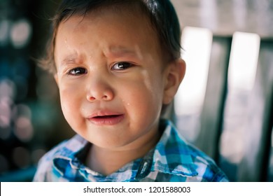 Young latino son, toddler age crying with tears in eyes looking lost or worried  with menacing looking background, expressing missing or hurt children