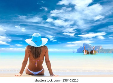 Young Latino woman reaxing on the beach at exotic resort