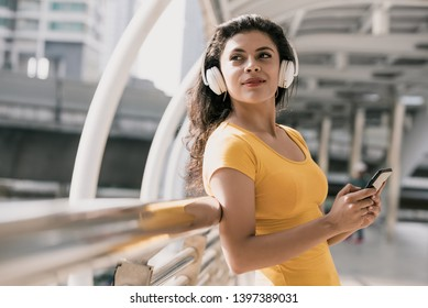 Young Latino woman wearing bluetooth headphones listening to music in the city