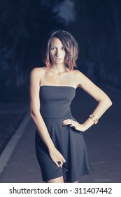 Young latino  women in short black dress is posing outdoors in night time (or late evening) in fashion manner with her hand on waist. She is lit by street lamp from the front side. Alley on background