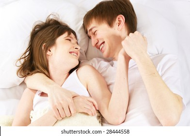 young laughing couple in bed