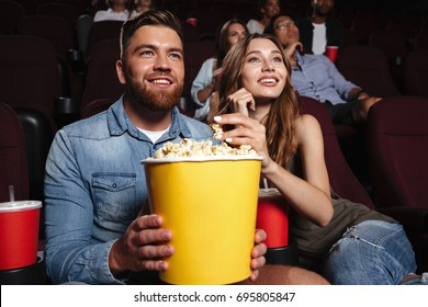 Young laughing couple holding a big popcorn bucket while watching a movie at the cinema