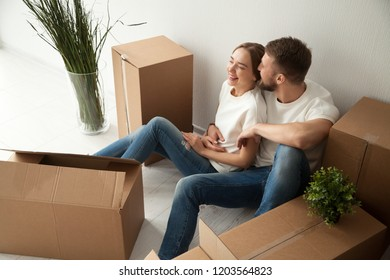 Young laughing couple sitting on floor, embracing in new apartment with packaged belongings in cardboard boxes, family just arrived in new own house, man and woman beginning live together, having fun