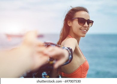 Young laughing girl wering in bikini outstretching hand asking to follow her on background of sea. focus on the woman