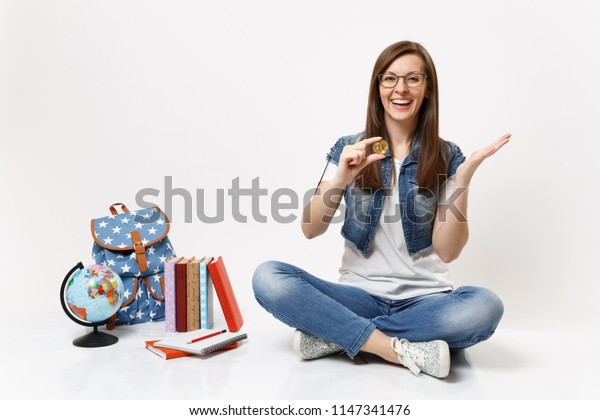 Young laughing happy woman student in glasses holding bitcoin spreading hands sit near globe, backpack, school books isolated on white background. Education in high school university college concept