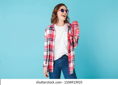 Young laughing lady in sunglasses standing with pink sport bottle on over blue background Pretty girl in plaid shirt and jeans