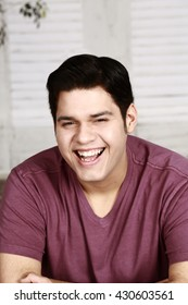 young laughing latino man in red shirt