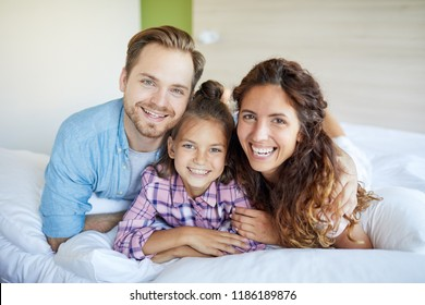 Young laughing restful couple and their daughter in casualwear lying on bed