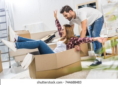 Young laughing woman sitting in a cardboard box while her boyfriend is pushing it