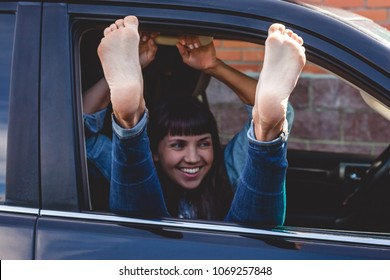 Young laughing woman sitting in the front seat of the car sticking out her bare feet in the window.