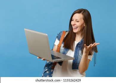 Young laughing woman student in denim clothes with backpack hold using working on laptop pc computer spreading hands isolated on blue background. Education in university. Copy space for advertisement