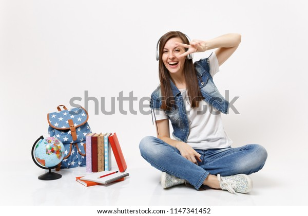 Young laughing woman student with headphones listening music showing victory sign sitting near globe, backpack, school books isolated on white background. Education in high school university college