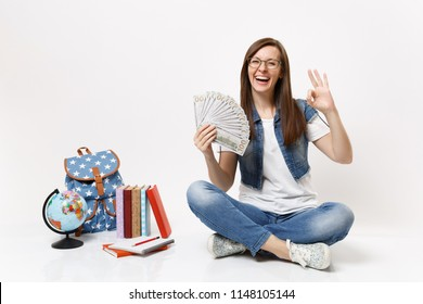 Young laughing woman student holding bundle lots of dollars, cash money showing OK sign sit near globe, backpack school books isolated on white background. Education in high school university college