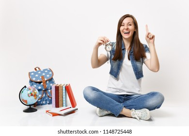 Young laughing woman student pointing index finger up holding alarm clock sitting near globe, backpack, school books isolated on white background. Education in high school university college concept