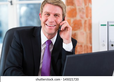Young lawyer working in his Office, he sitting on the desk and on the telephone is a customer or client
