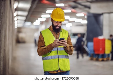 Young lazy bearded worker in vest, with helmet on head standing inside of building in construction process and hanging on social media.