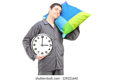 A young lazy guy holding a wall clock and sleeping on a pillow isolated agaist white background
