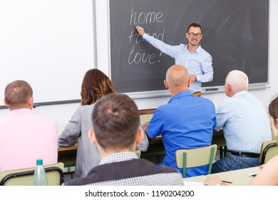 Young lecturer talking to mixed age  students during seminar