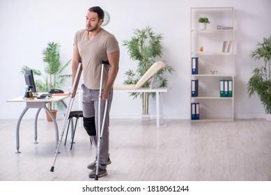 Jeune homme blessé à la jambe avec des béquilles