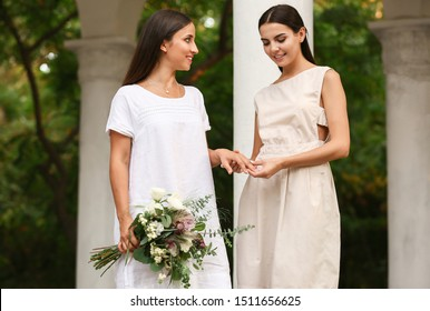 Young lesbian couple exchanging rings during wedding ceremony outdoors