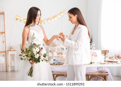 Young lesbian couple exchanging rings during wedding ceremony