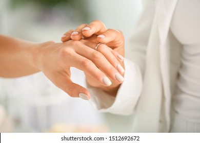 Young lesbian couple exchanging rings during wedding ceremony, closeup