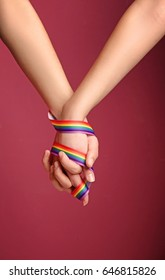 Young lesbian couple with rainbow ribbon on color background