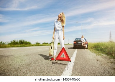 The young lesbian's couple broke down the car while traveling on the way to rest. Trying to fix the broken by their own or should hitchhike, getting nervous. Relationship, troubles on the road
