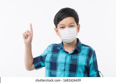 Young little Asain boy wearing surgical protective mask on face on white background and look at camera and point finger to black space
