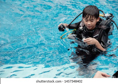 Young little Asian boy scuba diver beginner checking pressure gauge and holding regulator, diving lessons for beginners, preteen teen travel