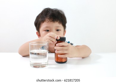 Young little Asian boy taking table medicine with a glass of water. Healthcare and Medical concept.