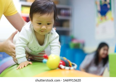 Young little Asian cute baby crawling on circular cushion practicing balance the body teaching by her preschool teacher in gym. The kid looking at toy and trying to catch it. Play and learn concept.