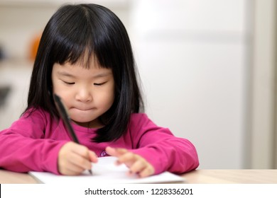 Young little Asian girl learning to write on piece of paper