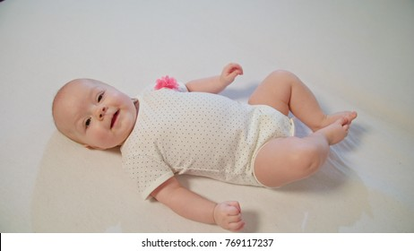 A young little baby is laying on a white blanket and looking around