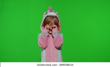 Young little blonde child 5-6 years old in unicorn costume crying, wiping tears with her hands on chroma key background. Portrait of kid girl animator in unicorn pajamas. Copy space
