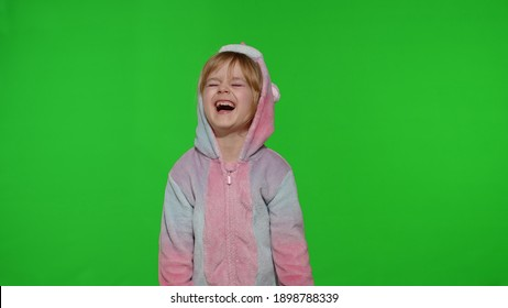 Young little blonde child 5-6 years old in unicorn costume crying with tears on chroma key background. Portrait of kid girl animator in unicorn pajamas. Copy space