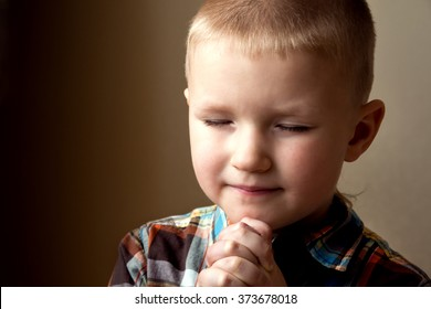 Young little boy (child, kid) spiritual peaceful praying and wishing, close up portrait with copy space.