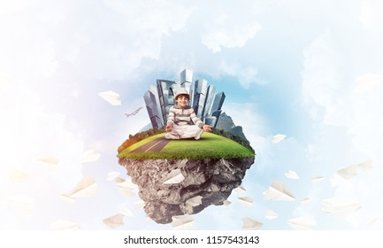 Young little boy keeping eyes closed and looking concentrated while meditating on flying island among flying paper planes with cloudy skyscape on background. 3D rendering.