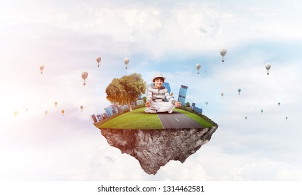 Young little boy keeping eyes closed and looking concentrated while meditating on flying island in the air with cloudy skyscape and flying aerostats on background. 3D rendering.