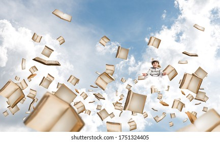 Young little boy keeping eyes closed and looking concentrated while meditating among flying books in the air with cloudy skyscape on background.