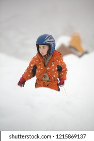 Young little boy in orange overall and blue helmet plays outdoor at winter time.