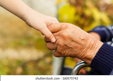 Young little boy shaking hands with old man.