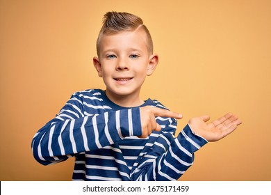 Young little caucasian kid with blue eyes wearing nautical striped shirt over yellow background amazed and smiling to the camera while presenting with hand and pointing with finger.