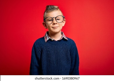 Young little caucasian kid with blue eyes standing wearing smart glasses over red background with serious expression on face. Simple and natural looking at the camera.