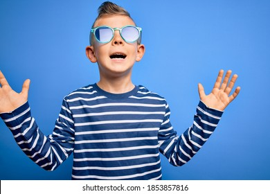 Young little caucasian kid with blue eyes standing wearing sunglasses over blue background celebrating mad and crazy for success with arms raised and closed eyes screaming excited. Winner concept